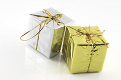 Gift boxes, gold and silver. Two gift boxes, gold and silver colored on a hi-key isolated white background. Contains copy space Stock Image
