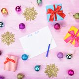 Christmas wish list on pink background. Gift boxes, golden snowflakes, colorful baubles Flat lay Stock Images