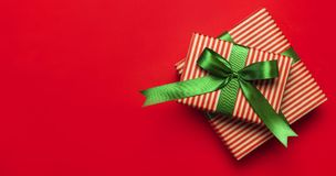 Gift boxes with green ribbon on red background top view flat lay. Holiday concept, new year or Christmas gift box, presents Xmas h. Oliday. Congratulations stock photography