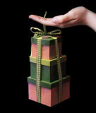 Gift boxes in hand. On balck Royalty Free Stock Image