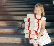 Gift boxes in the hands of little cute girl Royalty Free Stock Images