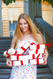 Gift boxes in the hands of young blond woman Stock Image