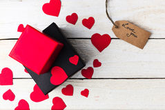 Gift boxes and heart papercut on wooden background Royalty Free Stock Images