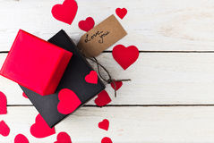 Gift boxes and heart papercut on wooden background Royalty Free Stock Image