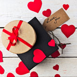 Gift boxes and heart papercut on wooden background Royalty Free Stock Photo