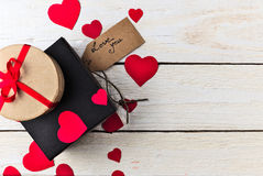 Gift boxes and heart papercut on wooden background Stock Photos