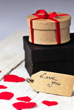 Gift boxes and heart papercut on wooden background Royalty Free Stock Photography