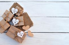 Gift boxes with hearts hand made on a light wooden background. Celebratory background. Royalty Free Stock Image