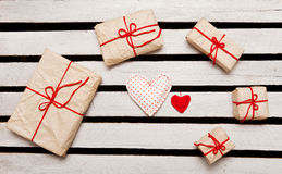 Gift boxes and hearts on white wooden background Royalty Free Stock Images