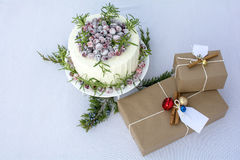 Gift boxes and homemade white chocolate cranberry cake. White chocolate cranberry cake decorated with sparkling sugar coated fresh cranberries, Holiday cake Stock Photos