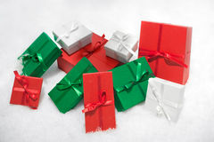 Gift boxes isolated on white background in snow. Royalty Free Stock Photos