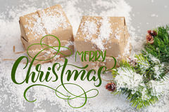Gift boxes of kraft paper with spruce branches and text Merry Christmas. Calligraphy lettering.  Stock Photos