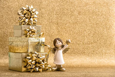 Gift boxes and little angel on bright golden background Royalty Free Stock Photos