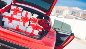 Gift boxes in a luggage carrier of the red car. White boxes with gifts tied with red ribbons with large red bows and a huge bouquet of red roses,neatly stacked Royalty Free Stock Photography