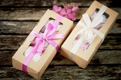 Gift boxes of marshmallows from the confectioner, a compliment.On a wooden background. Romance. Gift boxes of marshmallows from the confectioner, a compliment stock images