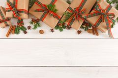 Colorful present boxes for any holiday on wooden background. Gift boxes, nuts, small bells and fir tree twigs border, top view with copy space on wood table Royalty Free Stock Photography