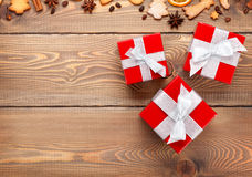 Gift boxes over christmas wooden background with spices and ging Stock Photography