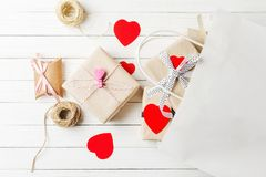 Free Gift Boxes, Paper Cut Heart And Shopping Bag On A White Wooden Background. Valentine`s Day Decorations Royalty Free Stock Photo - 134515775