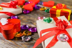 Gift boxes papier mache in the form of red hearts tied with satin ribbons and gifts Packed by craft paper on the wooden table. Royalty Free Stock Image