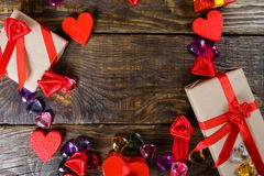 Gift boxes papier mache in the form of red hearts tied with satin ribbons and gifts Packed by craft paper on the wooden table. Stock Photography
