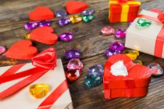 Gift boxes papier mache in the form of red hearts tied with satin ribbons and gifts Packed by craft paper on the wooden table. Stock Photos