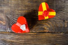 Gift boxes papier mache in the form of red hearts tied with satin ribbons and gifts Packed by craft paper on the wooden table. Stock Photo