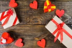 Gift boxes papier mache in the form of red hearts tied with satin ribbons and gifts Packed by craft paper on the wooden table. Stock Images