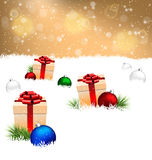 Gift boxes with pine and Christmas balls on snow on gold Stock Image