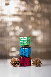 Gift boxes and pine cones. Consecutive Three gift boxes and two pine cones on a bokeh background Stock Image