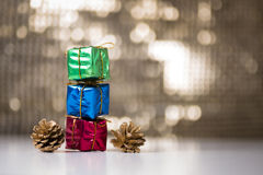 Gift boxes and pine cones. Consecutive Three gift boxes and two pine cones on a bokeh background Royalty Free Stock Photo