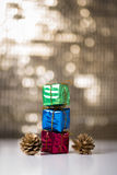 Gift boxes and pine cones. Consecutive Three gift boxes and two pine cones on a bokeh background Royalty Free Stock Images