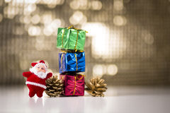 Gift boxes and pine cones. Consecutive Three gift boxes, two pine cones and miniature Santa Claus on a bokeh background Royalty Free Stock Image