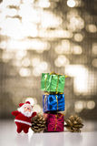 Gift boxes and pine cones. Consecutive Three gift boxes, two pine cones and miniature Santa Claus on a bokeh background Stock Photo