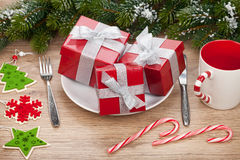 Gift boxes on plate, fir tree and christmas decor Stock Photos