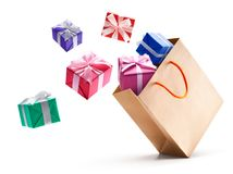 Gift boxes pop out from shopping bag. Isolated on white background Royalty Free Stock Photo