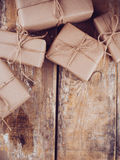 Gift boxes, postal parcels on wooden board. Several gift boxes, postal parcels wrapped in brown kraft paper tied with a rope on a wooden board stock images