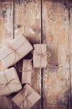 Gift boxes, postal parcels on wooden board. Several gift boxes, postal parcels wrapped in brown kraft paper tied with a rope on a wooden board stock photography