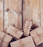 Gift boxes, postal parcels on wooden board. Several gift boxes, postal parcels wrapped in brown kraft paper tied with a rope on a wooden board royalty free stock images