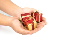 The gift boxes red & gold color in hand give for you on white background. Isolated, Christmas holiday and party decoration Royalty Free Stock Images