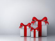 Gift boxes with red ribbon bow and empty white wall Stock Images