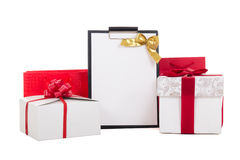 Gift boxes with red ribbon and wish list on white background Stock Image