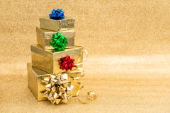 Gift boxes ribbon bow golden background Holidays decoration. Gift boxes with ribbon bow on golden background. Holidays decoration Royalty Free Stock Photos