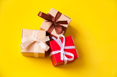 Gift boxes with ribbon bows. Three wrapped colorful gift boxes with colorful satin ribbons and bows on yellow background in studio, Focus on a bow Stock Photography