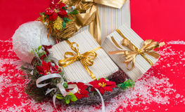 Gift boxes with ribbon and wreath with poinsettia flowers on a r Royalty Free Stock Images