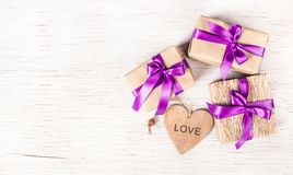 Gift boxes with satin ribbons on a white wooden background. Wooden heart. Romantic concept. Valentine`s Day. Royalty Free Stock Image