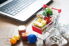 Gift boxes in shopping cart and Christmas decorations with laptop computer on wood table Royalty Free Stock Photography