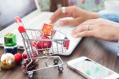 Gift boxes in shopping cart and Christmas decorations on table, Woman using laptop in background, Online shopping Royalty Free Stock Photos