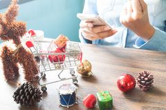 Gift boxes in shopping cart and Christmas decorations on table, Woman using mobile device, Online shopping Stock Photography