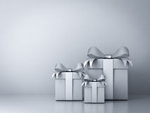 Gift boxes with silver ribbon bow and empty white wall Royalty Free Stock Images
