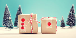 Gift boxes in a snow covered miniature forest Royalty Free Stock Images